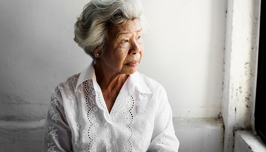 Elderly lady looking out a window