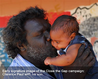 Indigenous father holding up his baby with a kiss