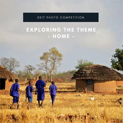 Photo of Ugandan boys in school uniform walking through grass-roofed village. Artist Richard Wainwright title  Post War Education,