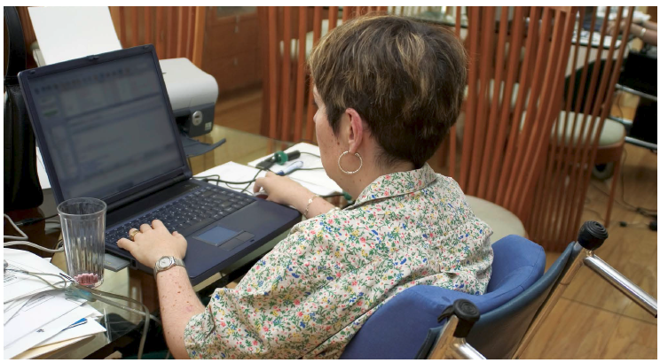 Officer worker in wheelchair using computers