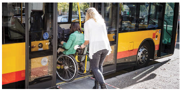 Person with wheelchair using ramp to access bus