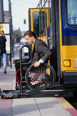 Man in wheelchair getting off bus
