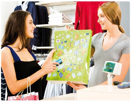 A sales lady giving a shopping bag to the female customer