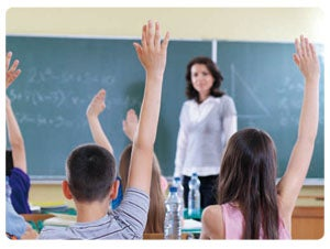 Kids in the classroom with one hand up in front of a female teacher