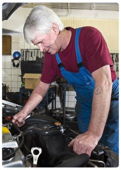 An elderly man working on the car engine