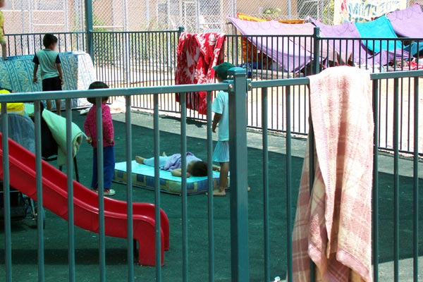 Children in playground at Woomera with hunger strike in background, January 2002.
