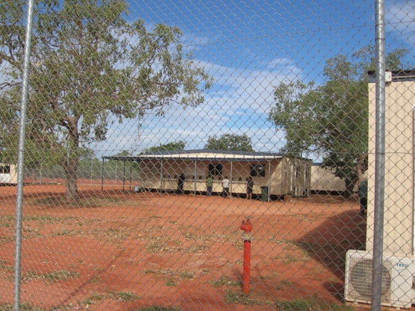 People in detention using outdoor telephones, Curtin IDC