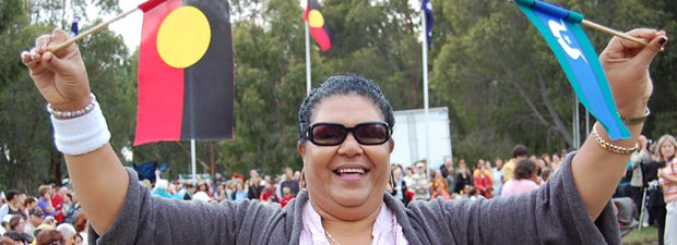 Aboriginal lady holding the Aboriginal flag