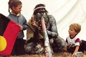 Aboriginal man playing didgeridoo with young girl holding the Aboriginal flag and little boy looking on