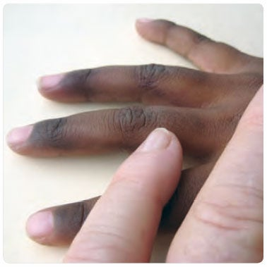 White person and Indigenous person's hands together