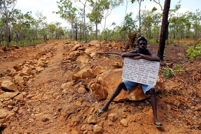 Intervention by Belinda Mason. Indigenous man holding sign on a road in the bush