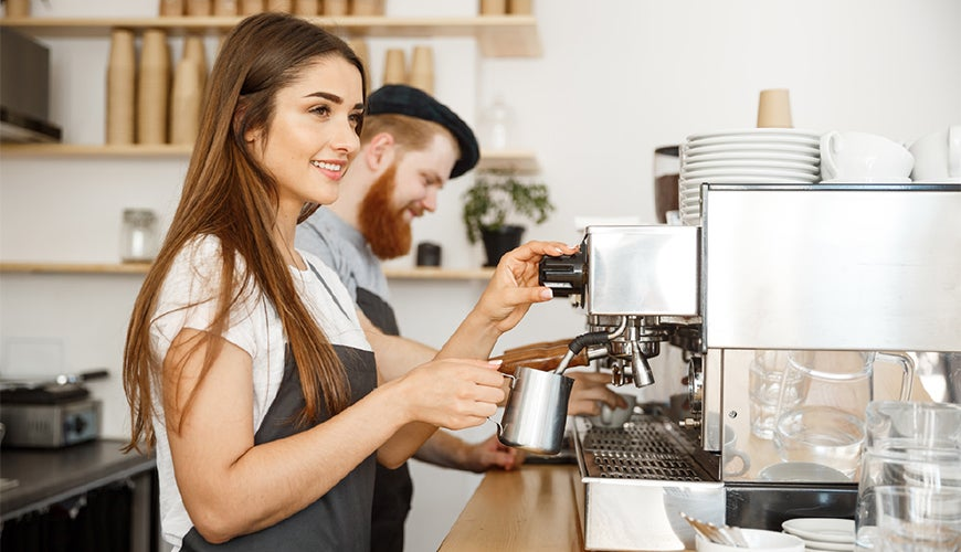 Male and female baristas in a cafe