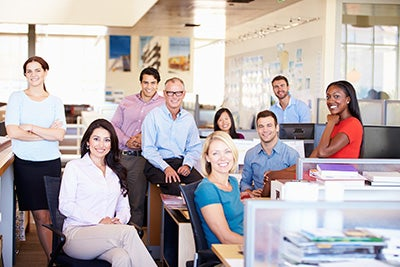 Large group of office workers standing and sitting in office