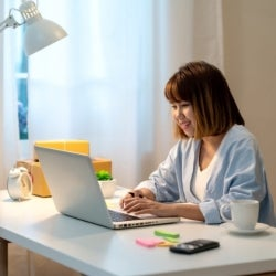 An asian lady working from home on her desk