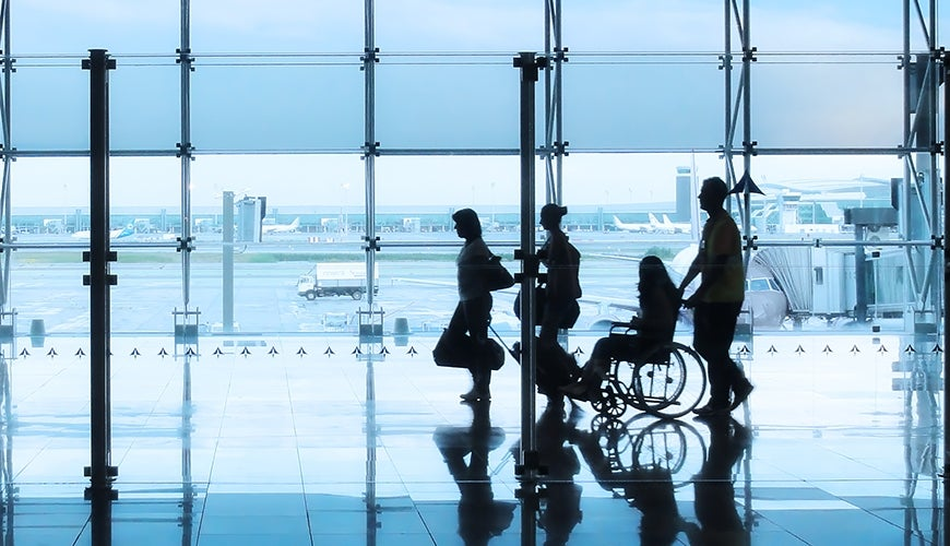 family including person using a wheelchair walking through an airport