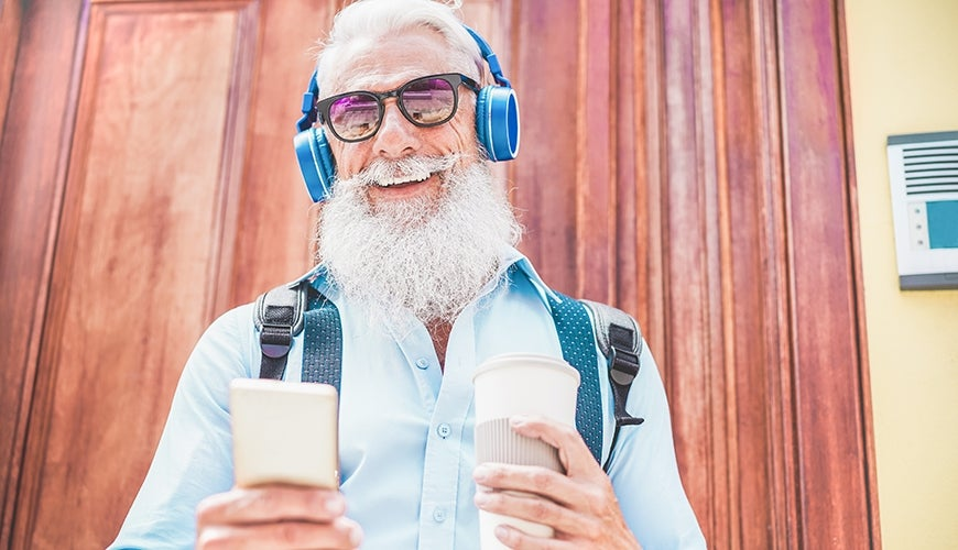 older man enjoying music and drinking coffee