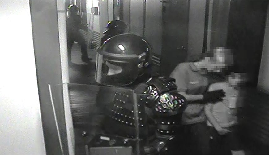 still from incident video: guard in body armour on alert and another guard leads child away
