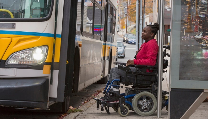 Woman with cerebral palsy using a wheelchair to get onto the bus