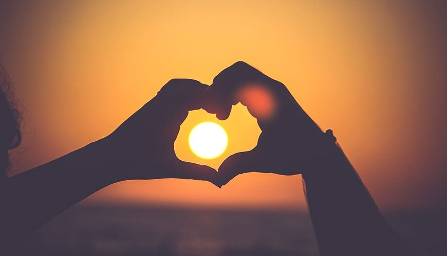 Hands framing a heart over a sunset
