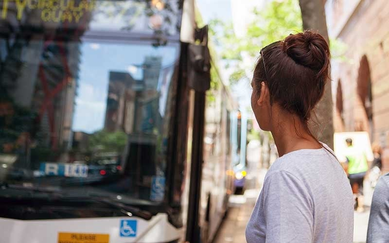 A young woman waits for a bus on a city street.
