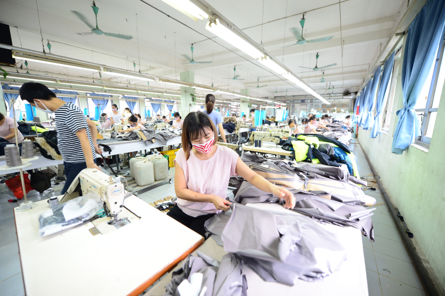 Image of garment factory, with woman in the foreground at sewing machine