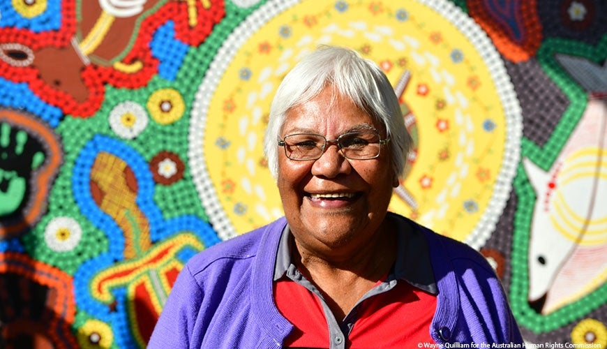 Jenny Ebsworth smiling in front of Aboriginal Art.
