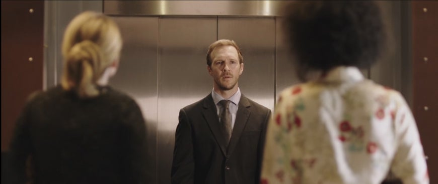man starting at two women outside an elevator