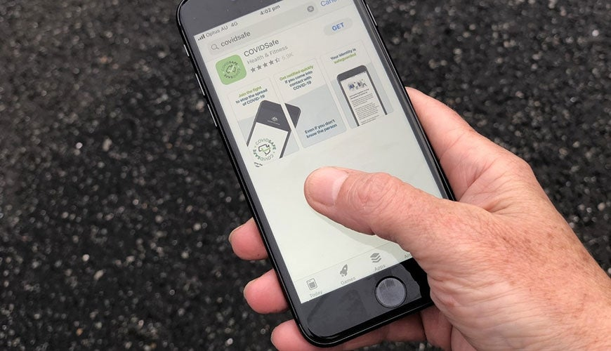 COVIDSafe App - hand holding iphone with the COVID-19 application