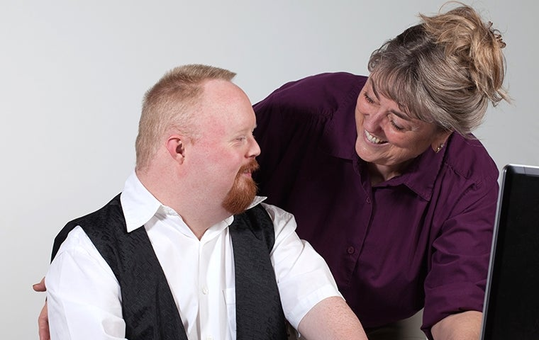Worker with Down Syndrome and co-worker. Image from iStock.