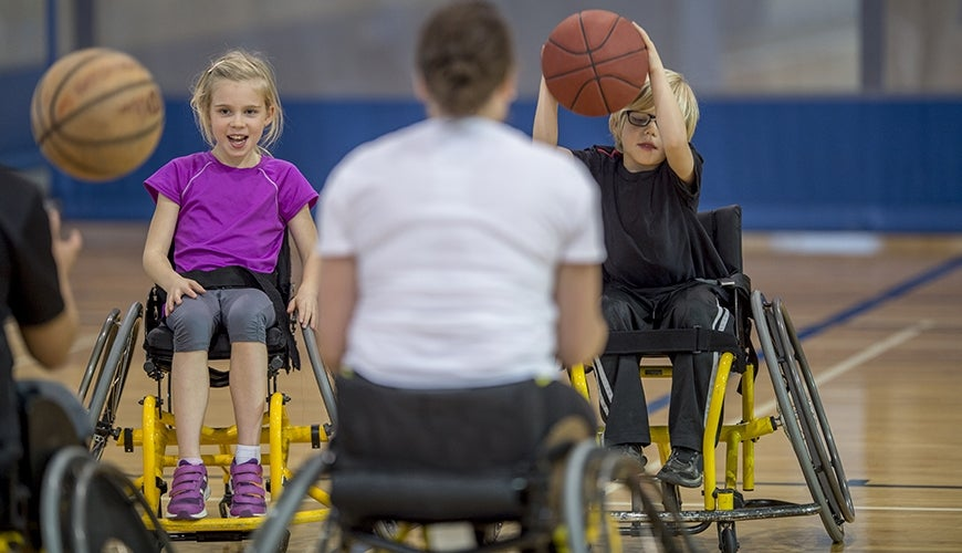 kids on a wheelchair playing basketball