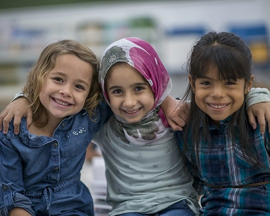 three young girls, one who is Muslim, happy at school