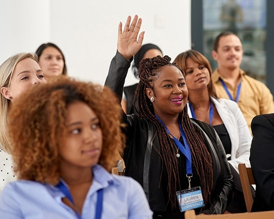 black woman holds hand up in adult education class
