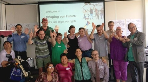 Happy group of participants waving at the Welcome to Shaping our Future disability consultation