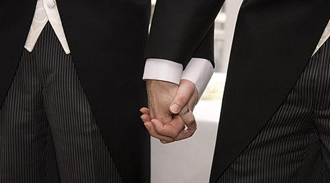 Two men holding hands, getting married