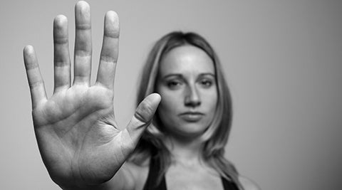 Women holding hand in stop position.