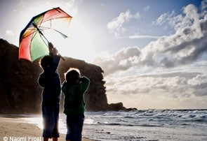 Photo: Children on a beach with an umbrella