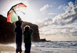 Photo: Children on a beach with an umbrella