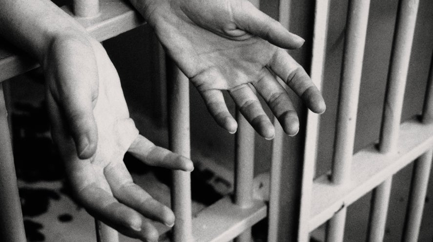 Hands reaching out through prison bars