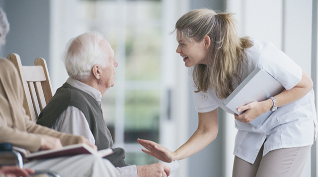Aged care worker talking to male resident