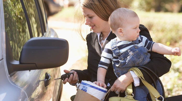 Working mother holding her keys, baby, groceries and trying to get into her car