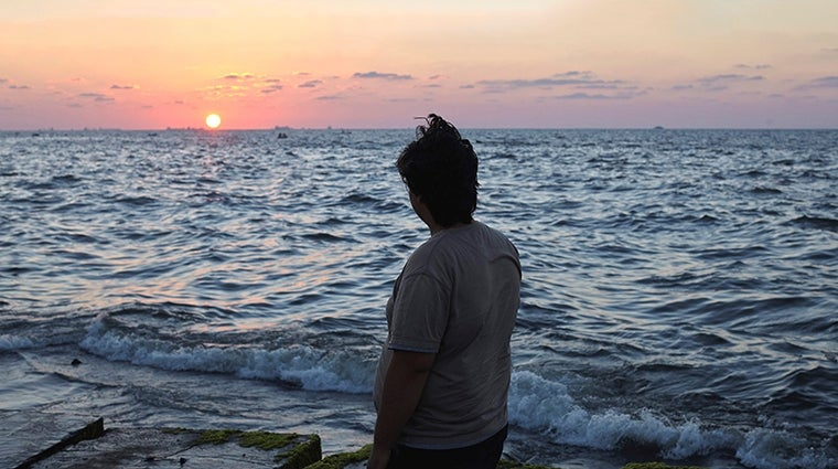 Refugee stares out to sea. Photo UNHCR & Shawn Baldwin