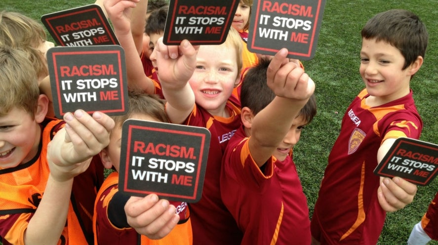 young boys wearing football jerseys holding campaign coasters