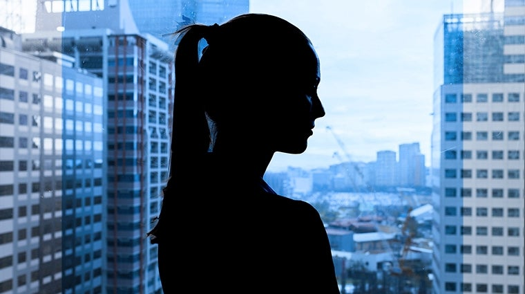 Silhouette of young woman looking out a window