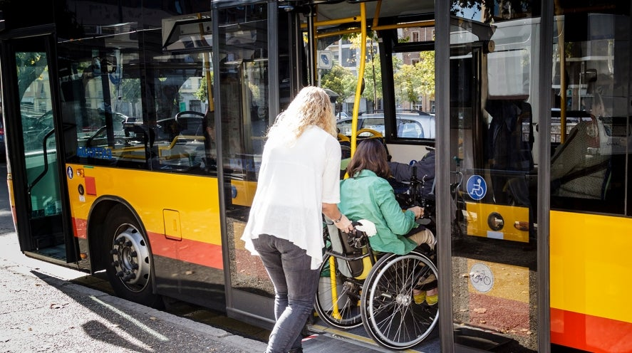 Person in a wheelchair entering a bus with a carer