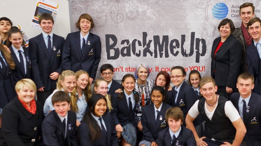 Ruby Rose with school children in a group shot around a BackMeUp banner