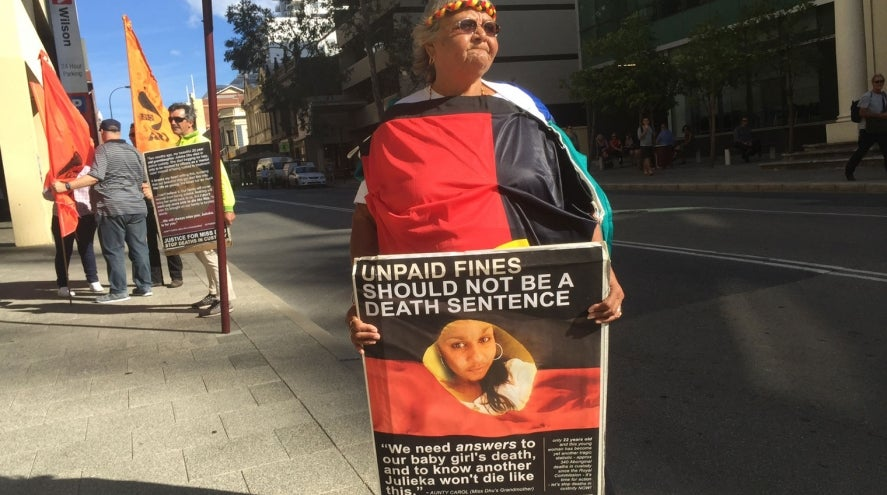 "Ms Dhu's grandmother, Carol Roe holding a sign, 'UNPAID FINES SHOULD NOT BE A DEATH SENTENCE', ""We need answers to our baby girl's death, and to know another Julieka won't die like this."""