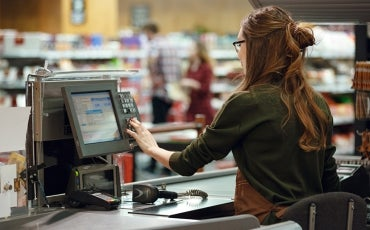 Woman at shop, working the till
