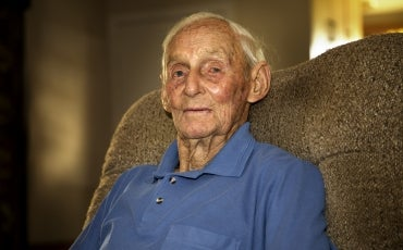An elderly man sitting on a sofa at home, looking into the camera.