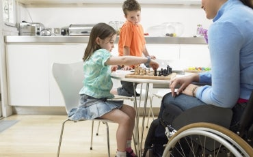 A woman using a wheelchair is at a table with two young children at home playing a game.