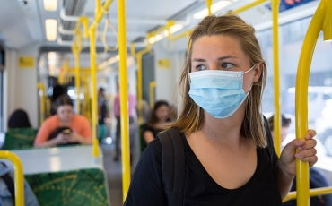 Woman on train in mask